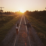 Couple Walking on Railroad Tracks Holding Hands Photographic Print by Dennis Hallinan