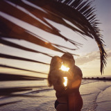 Couple Embracing Next to Palm Tree at Sunset Photographic Print by Dennis Hallinan