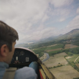 Man in Airplane Cockpit Looking Out at Fields Below Photographic Print by Dennis Hallinan