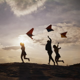 Three Friends Running Flying Kites Photographic Print by Dennis Hallinan