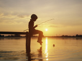 Boy Sitting on Pier Fishing at Sunset Photographic Print by Dennis Hallinan