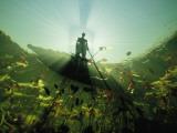 A Bushman in a Canoe Peering Down into Flood Waters of the Okavango Fotografisk tryk af David Doubilet
