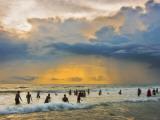 Indian Bathers Playing in Surf During Cloudy Sunset Lámina fotográfica por Tim Makins