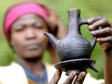 Dorze Woman with Black Coffee Pot Valokuvavedos tekijänä Tom Cockrem