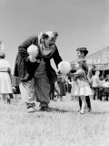 Clown Handing Cotton Candy To Children Outside Circus Tent Reproduction photographique par H. Armstrong Roberts