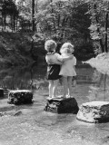Boy and Girl Standing on Rock Path in Stream, With Arms Around Each Other Photographic Print by H. Armstrong Roberts