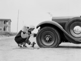 Woman Changing Flat Tire on Car Fotografie-Druck von H. Armstrong Roberts