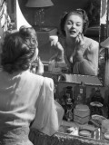 Woman Applying Make-Up in Front of Mirror Photographic Print by George Marks