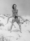 Young Couple on Beach, Woman Leap-Frogging Man, Portrait Photographic Print by George Marks