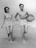 Young Couple Running on Beach With Beach Ball Photographic Print by George Marks