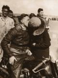 Woman Kissing Motorcycle Racer Fotografie-Druck
