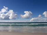 Gentle Waves and Surf Surging onto a Flat Beach under Puffy Clouds Fotografisk tryk af Charles Kogod