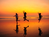 Silhouetted Children Playing on the Beach at Sunset Fotografisk tryk af Jorge Fajl