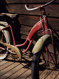 A Very Old Red Girls' Bike Rests on an Old Wooden Porch Fotografisk trykk av Paul Damien