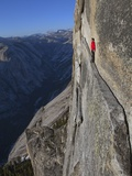 A climber walks a 40-foot-long sliver of granite on Half Dome, named the Thank God Ledge. Stretched Canvas Print by Jimmy Chin