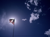 An American Flag Against a Glowing Sun Photographic Print by Aaron Huey