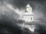 Lighthouse Emerging From Dark Clouds Photographic Print by Paul Hardy