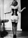 Young Woman Lacing Her Corset Fotografisk trykk av  Bettmann