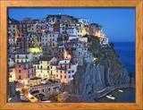 Iltahämärä laskeutuu mäenrinteessä olevaan kaupunkiin, josta on näkymä Välimerelle, Manarola, Cinque Terre, Italia Kehystetty valokuvavedos tekijänä Dennis Flaherty
