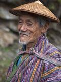 A Wizened Old Farmer Near Mongar Wears the Traditional Knee-Length National Robe Called Gho and a B Lámina fotográfica por Nigel Pavitt