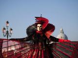 Venice, Veneto, Italy, a Mask in Costume on the Bacino Di San Marco with the Cupola of Santa Maria  Lámina fotográfica por Ken Scicluna