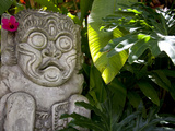 Bali, Ubud, a Stone Carving, Adorned with a Hibiscus Flower, Sits in Tropical Gardens Fotografie-Druck von Niels Van Gijn