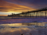 A Lone Surfer Waits for a Wave a People Stroll the Pier Watching a Brilliant Sunset, Oceanside Photographic Print by Patrick Smith