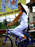 Vietnamese woman cycles in white clothes and hat Photographic Print by Charles Bowman