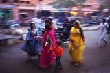 Indian women in colourful saris walk along streets Photographic Print by Charles Bowman