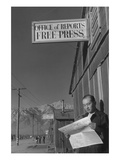 Roy Takeno Reading Paper in Front of Office Posters af Ansel Adams