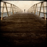 A Long Wooden Walkway at the Sea with a Figure Standing in the Distance Stampa fotografica di Luis Beltran