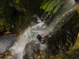 A Canyoneer Endures the Deluge of a Waterfall in Empress Canyon Fotografisk trykk av Peter Carsten