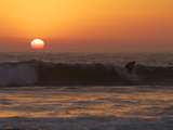 Surfer Riding a Wave at Sunset over the Pacific Ocean Stampa fotografica di Tim Laman