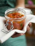 Hands Holding Preserving Jar of Tomato Sauce