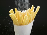 Sprinkling Salt over Chips Fotografie-Druck