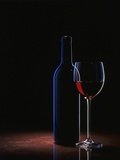 A Glass of Red Wine and a Wine Bottle Photographic Print by Roland Krieg