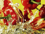 Peppers Falling into Water Against Yellow Background Photographic Print by Michael Meisen