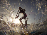A Stand Up Paddleboarder Surfs a Wave Near Nags Head Pier Impressão fotográfica por Skip Brown