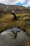 A Young Girl Leaps Over a Stream During a Trek Fotografisk trykk av Beth Wald