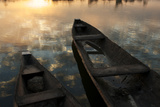 Sunlight and Clouds Reflecting in Calm Water Near Canoes Photographic Print by Cristina Mittermeier