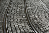 A Railway Tracks Running Through a Cobblestone Street Photographic Print by Joe Petersburger