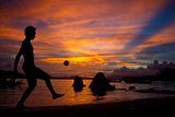 A Solomon Islander Kicks a Ball Against a Stunning Sunset Off Tetapare Fotografisk trykk av Robin Moore