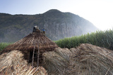 Men Stand on a Thatched Roof of a Hut, the Bale Mountains Are in Back Photographic Print by Aaron Huey
