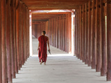 Monk in Walkway of Wooden Pillars To Temple, Salay, Myanmar (Burma) Reproduction photographique par Peter Adams