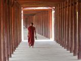 Monk in Walkway of Wooden Pillars To Temple, Salay, Myanmar (Burma) Fotografie-Druck von Peter Adams