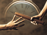 Close Up of Two Runners Hands Passing the Baton in Relay Race in Front of Old European Clock Face Photographic Print