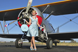 Elegant 1940's Style Pin-Up Girl Standing in Front of an F3F Biplane Fotografisk trykk