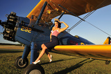 1940's Style Pin-Up Girl Sitting on the Wing of a Stearman Biplane Fotografisk tryk