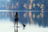A Paddle Boarder Paddling on a Still Lake in Autumn Stampa fotografica di Robbie George