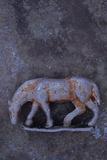 Battered Lead Model of Grazing Horse Lying on Tarnished Metal Fotografisk trykk av Den Reader